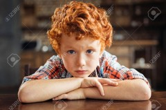 Upset little kid resting his chin on his folded arms